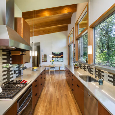 Example of a large trendy galley medium tone wood floor and beige floor eat-in kitchen design in Portland with flat-panel cabinets, gray backsplash, ceramic backsplash, no island, an undermount sink, medium tone wood cabinets, stainless steel appliances and solid surface countertops