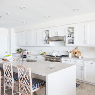 Beach style kitchen appliance - Example of a coastal galley light wood floor and beige floor kitchen design in San Diego with white cabinets, white backsplash, subway tile backsplash, stainless steel appliances, an island, an undermount sink and shaker cabinets