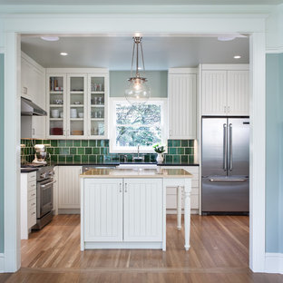 Mid-sized ornate u-shaped light wood floor enclosed kitchen photo in Portland with a farmhouse sink, glass-front cabinets, white cabinets, granite countertops, green backsplash, ceramic backsplash, stainless steel appliances and an island