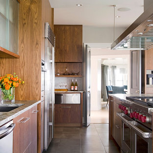 Expansive transitional galley eat-in kitchen in Boston with an undermount sink, flat-panel cabinets, dark wood cabinets, recycled glass benchtops, white splashback, glass tile splashback, stainless steel appliances, slate floors and with island.