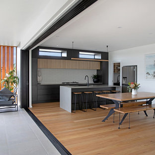 This is an example of a contemporary kitchen in Central Coast with flat-panel cabinets, subway tile splashback, with island and grey benchtop.