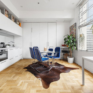 This is an example of a scandinavian eat-in kitchen in Melbourne with flat-panel cabinets, white cabinets, mirror splashback, light hardwood floors, beige floor and grey benchtop.