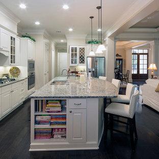 Пример оригинального дизайна: большая параллельная кухня-гостиная в стиле неоклассика (современная классика) с тройной раковиной, фасадами с выступающей филенкой, белыми фасадами, гранитной столешницей, серым фартуком, фартуком из каменной плитки, техникой из нержавеющей стали, темным паркетным полом, островом и черным полом