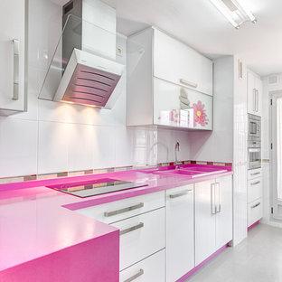 マラガの中くらいのコンテンポラリースタイルのおしゃれなキッチン (フラットパネル扉のキャビネット、白いキャビネット、白いキッチンパネル、ダブルシンク、人工大理石カウンター、セラミックタイルのキッチンパネル、シルバーの調理設備、セラミックタイルの床、アイランドなし、ピンクのキッチンカウンター) の写真