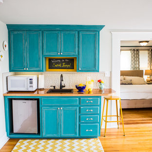 Small traditional open concept kitchen ideas - Example of a small classic single-wall medium tone wood floor open concept kitchen design in Austin with a single-bowl sink, recessed-panel cabinets, turquoise cabinets, wood countertops, gray backsplash and metal backsplash
