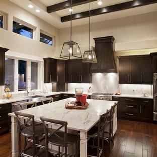 Idee per una cucina a U minimal con lavello stile country, ante in stile shaker, ante in legno bruno, paraspruzzi bianco, elettrodomestici in acciaio inossidabile, parquet scuro, un'isola e top in granito
