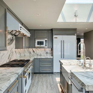 Große Klassische Wohnküche in L-Form mit Landhausspüle, Schrankfronten mit vertiefter Füllung, grauen Schränken, Küchenrückwand in Grau, Rückwand aus Stein, weißen Elektrogeräten, hellem Holzboden, Kücheninsel, Marmor-Arbeitsplatte und beigem Boden in Los Angeles