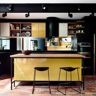 This is an example of a mid-sized eclectic l-shaped eat-in kitchen in Melbourne with flat-panel cabinets, yellow cabinets, with island, an undermount sink, wood benchtops, black splashback, mirror splashback, brick floors and stainless steel appliances.