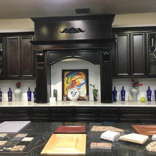 ロサンゼルスの中サイズのヴィクトリアン調のおしゃれなキッチン (フラットパネル扉のキャビネット、濃色木目調キャビネット、珪岩カウンター、パネルと同色の調理設備) の写真