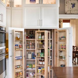 Idée de décoration pour une grand arrière-cuisine champêtre avec un placard avec porte à panneau encastré, des portes de placard blanches, un électroménager en acier inoxydable, un sol en bois brun et un îlot central.