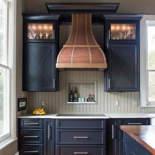 Inspiration för lantliga kök, med luckor med infälld panel, svarta skåp, bänkskiva i kalksten, mellanmörkt trägolv och en köksö