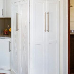 Imagen de cocina de estilo de casa de campo, grande, cerrada, con fregadero sobremueble, armarios estilo shaker, puertas de armario blancas, encimera de piedra caliza, salpicadero gris, electrodomésticos de acero inoxidable, suelo de madera en tonos medios y una isla