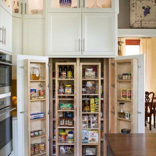 アトランタの広いカントリー風おしゃれなキッチン (エプロンフロントシンク、シェーカースタイル扉のキャビネット、白いキャビネット、ライムストーンカウンター、シルバーの調理設備、無垢フローリング) の写真