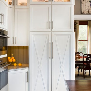 Photo of a large country separate kitchen in Atlanta with a farmhouse sink, shaker cabinets, white cabinets, limestone benchtops, green splashback, stainless steel appliances, medium hardwood floors and with island.