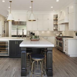 Offene Klassische Küche mit Landhausspüle, Schrankfronten im Shaker-Stil, Küchenrückwand in Beige, Küchengeräten aus Edelstahl, braunem Holzboden, Kücheninsel, braunem Boden und weißer Arbeitsplatte in Los Angeles