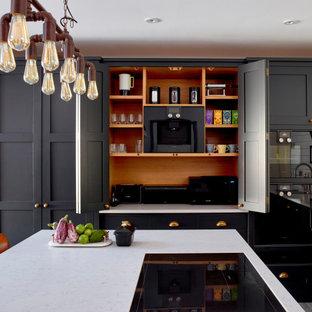 ロンドンの中サイズのインダストリアルスタイルのおしゃれなキッチン (ドロップインシンク、シェーカースタイル扉のキャビネット、黒いキャビネット、珪岩カウンター、白いキッチンパネル、サブウェイタイルのキッチンパネル、黒い調理設備、グレーの床、白いキッチンカウンター) の写真
