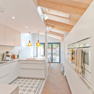 Photo of a contemporary u-shaped kitchen in Kent with flat-panel cabinets, white cabinets, white appliances, a breakfast bar, multi-coloured floors and white worktops.