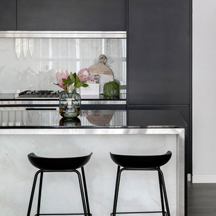 Photo of a contemporary kitchen in Sydney with flat-panel cabinets, black cabinets, stainless steel benchtops, white splashback, with island and brown floor.