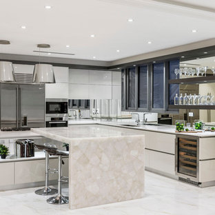 Photo of a contemporary l-shaped open plan kitchen in Brisbane with an undermount sink, flat-panel cabinets, white cabinets, quartz benchtops, metallic splashback, mirror splashback, stainless steel appliances, marble floors and with island.