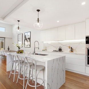 Inspiration for a contemporary galley open plan kitchen in Sydney with quartz benchtops, with island, a double-bowl sink, flat-panel cabinets, white cabinets, multi-coloured splashback, stone slab splashback, stainless steel appliances and medium hardwood floors.