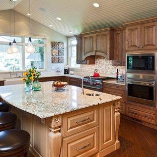 ボルチモアの大きいトラディショナルスタイルのおしゃれなキッチン (エプロンフロントシンク、濃色木目調キャビネット、御影石カウンター、黄色いキッチンパネル、パネルと同色の調理設備、レイズドパネル扉のキャビネット、磁器タイルのキッチンパネル、濃色無垢フローリング、茶色い床、ベージュのキッチンカウンター) の写真