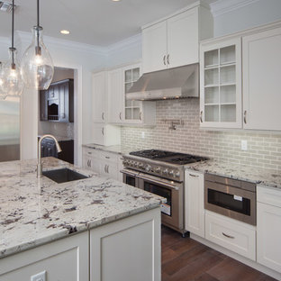 Photo of a large shabby-chic style galley open plan kitchen in Orlando with a drop-in sink, flat-panel cabinets, white cabinets, granite benchtops, grey splashback, subway tile splashback, stainless steel appliances, dark hardwood floors and multiple islands.