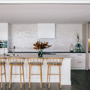 This is an example of a beach style galley kitchen in Sydney with an undermount sink, shaker cabinets, white cabinets, white splashback, panelled appliances, dark hardwood floors, with island, brown floor and black benchtop.