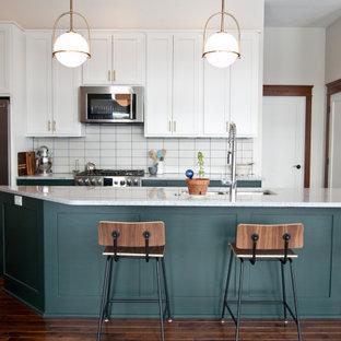Zweizeilige Klassische Küche mit Unterbauwaschbecken, Schrankfronten im Shaker-Stil, grünen Schränken, Küchenrückwand in Weiß, Küchengeräten aus Edelstahl, dunklem Holzboden, Kücheninsel, braunem Boden und weißer Arbeitsplatte in Sonstige
