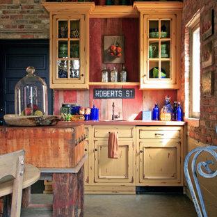 グランドラピッズの小さいカントリー風おしゃれなキッチン (シングルシンク、フラットパネル扉のキャビネット、ヴィンテージ仕上げキャビネット、人工大理石カウンター、赤いキッチンパネル、パネルと同色の調理設備、コンクリートの床) の写真