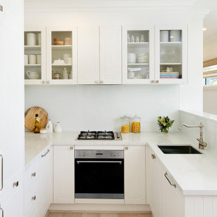 Small transitional u-shaped kitchen in Sydney with an undermount sink, louvered cabinets, white cabinets, white splashback, glass sheet splashback, no island, white floor and white benchtop.