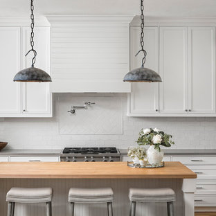 Large transitional kitchen ideas - Example of a large transitional l-shaped kitchen design in Austin with shaker cabinets, white cabinets, white backsplash, ceramic backsplash, stainless steel appliances, an island and wood countertops