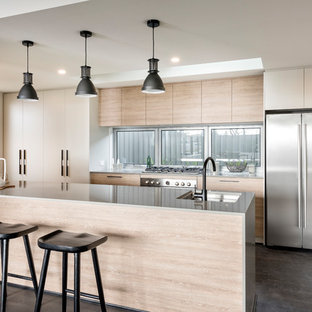 Inspiration for a contemporary galley separate kitchen with an undermount sink, flat-panel cabinets, light wood cabinets, window splashback, stainless steel appliances, dark hardwood floors, with island and grey floor.