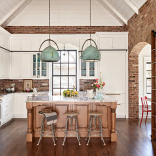 This is an example of a country l-shaped eat-in kitchen in Nashville with shaker cabinets, white cabinets, red splashback, brick splashback, panelled appliances, dark hardwood floors and with island.