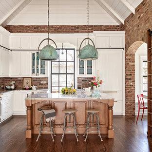 Landhausstil Wohnküche in L-Form mit Schrankfronten im Shaker-Stil, weißen Schränken, Küchenrückwand in Rot, Rückwand aus Backstein, Elektrogeräten mit Frontblende, dunklem Holzboden und Kücheninsel in Nashville