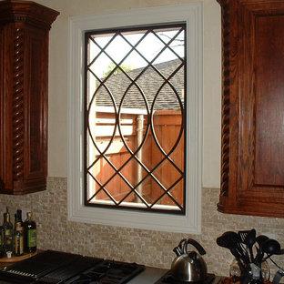 ダラスの中サイズの地中海スタイルのおしゃれなキッチン (落し込みパネル扉のキャビネット、中間色木目調キャビネット、御影石カウンター、ベージュキッチンパネル、ボーダータイルのキッチンパネル、シルバーの調理設備の) の写真