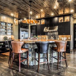 他の地域の広いラスティックスタイルのおしゃれなキッチン (シェーカースタイル扉のキャビネット、黒いキャビネット、シルバーの調理設備、濃色無垢フローリング、茶色いキッチンパネル、ボーダータイルのキッチンパネル、茶色い床、エプロンフロントシンク) の写真