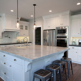 This is an example of a mid-sized arts and crafts u-shaped kitchen in Salt Lake City with a double-bowl sink, shaker cabinets, white cabinets, granite benchtops, white splashback, subway tile splashback, stainless steel appliances and with island.