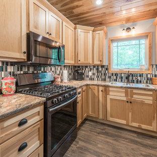 ミネアポリスの中サイズのラスティックスタイルのおしゃれなキッチン (アンダーカウンターシンク、シェーカースタイル扉のキャビネット、淡色木目調キャビネット、ラミネートカウンター、マルチカラーのキッチンパネル、モザイクタイルのキッチンパネル、シルバーの調理設備の、クッションフロア、茶色い床、マルチカラーのキッチンカウンター) の写真