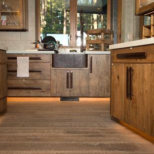 他の地域の広いインダストリアルスタイルのおしゃれなキッチン (エプロンフロントシンク、シェーカースタイル扉のキャビネット、中間色木目調キャビネット、クオーツストーンカウンター、白いキッチンパネル、セラミックタイルのキッチンパネル、シルバーの調理設備、淡色無垢フローリング) の写真