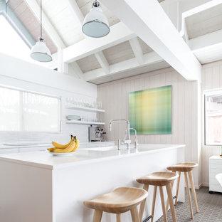 Réalisation d'une cuisine linéaire nordique avec un évier intégré, un placard à porte plane, des portes de placard blanches, une crédence blanche, moquette, un îlot central, un sol gris et un plan de travail blanc.