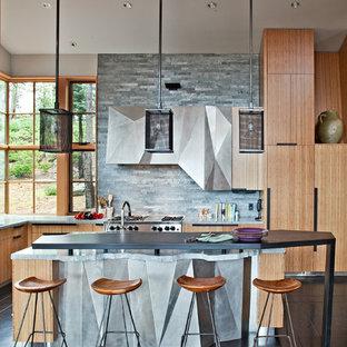 Imagen de cocina rústica con electrodomésticos de acero inoxidable, armarios con paneles lisos, puertas de armario de madera oscura, salpicadero verde y salpicadero de azulejos de piedra