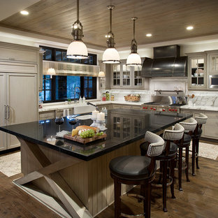 Kitchen - rustic l-shaped dark wood floor kitchen idea in Sacramento with a farmhouse sink, shaker cabinets, gray cabinets, white backsplash and paneled appliances