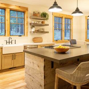 This is an example of a rustic kitchen in Phoenix with a belfast sink, shaker cabinets, medium wood cabinets, white splashback, stainless steel appliances, medium hardwood flooring, an island, brown floors and white worktops.