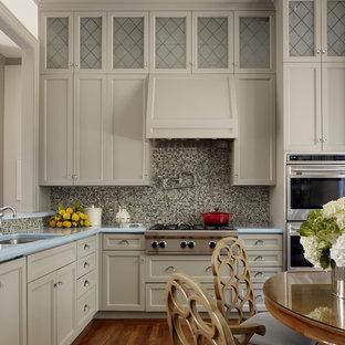 Imagen de cocina actual con salpicadero con mosaicos de azulejos, electrodomésticos de acero inoxidable y encimeras turquesas