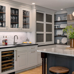 This is an example of a large transitional u-shaped eat-in kitchen in Boston with an undermount sink, recessed-panel cabinets, grey cabinets, soapstone benchtops, grey splashback, subway tile splashback, stainless steel appliances, medium hardwood floors, with island, beige floor and green benchtop.