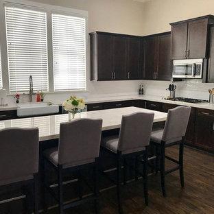 Mittelgroße Moderne Wohnküche in L-Form mit Unterbauwaschbecken, Quarzit-Arbeitsplatte, Küchenrückwand in Weiß, Rückwand aus Keramikfliesen, Küchengeräten aus Edelstahl, gebeiztem Holzboden, Kücheninsel, braunem Boden und weißer Arbeitsplatte in Dallas