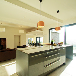 Inspiration for a large contemporary l-shaped eat-in kitchen in Cork with a drop-in sink, flat-panel cabinets, grey cabinets, quartz benchtops, brown splashback, ceramic splashback, black appliances, ceramic floors and with island.