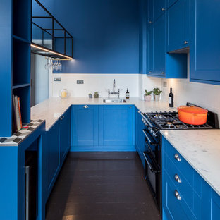 Inspiration for a traditional u-shaped kitchen in London with a submerged sink, shaker cabinets, blue cabinets, white splashback, metro tiled splashback, black appliances, a breakfast bar, brown floors and white worktops.