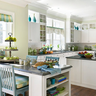 Inspiration for a large timeless u-shaped medium tone wood floor open concept kitchen remodel in Boston with an undermount sink, recessed-panel cabinets, white cabinets, granite countertops, white backsplash, subway tile backsplash, paneled appliances and an island