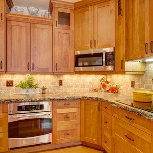 Offene, Große Klassische Küche in L-Form mit Doppelwaschbecken, Schrankfronten im Shaker-Stil, hellen Holzschränken, Granit-Arbeitsplatte, Küchenrückwand in Braun, Rückwand aus Steinfliesen, Küchengeräten aus Edelstahl, hellem Holzboden und Kücheninsel in Denver